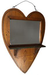 "E223 heart-form with applied mirror and shelf with red and green-painted arrow. Retains an old painted surface with later varnish. First quarter 20th century. 16"" L, 11"" W."