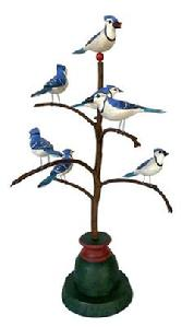 F630 American, 20th Century Folk Art Bird Tree, with seven beautiful polychrome painted and hand carved wooden Bluejays resting on a steamed and bent branch's in a colorful base