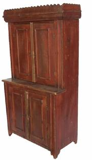 "Z20 DOLL SIZE STEPBACK CUPBOARD.   American, late 19th century, pine. Sawtooth cornice, two sets of blind doors, and cleaned down to reddish stain on the outside. Brown paint on the inside. 29.5""h. 16""w."