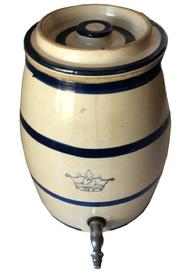 "C371  Stoneware crock having cream color glaze with cobalt blue bands and stenciled crown. Matching blue band lid. Metal spigot   Glazed stoneware. Metal spigot. Dimensions: Height: 12-3/4"". Width: 9-3/4"". Depth: 12-1/2"" (including spigot). Roseville, Ohio. c.1900-25.Very good condition"