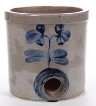 "E242 BALTIMORE, MARYLAND DECORATED STONEWAREDIMINUTIVE WATER COOLER, salt-glazed, approximately one-gallon capacity, cylindrical form with single incised ring and squared rim. Brushed cobalt upright double-blossom floral decoration on both sides, additional cobalt encircling bunghole. Probably the pottery of Peter Herrmann (1825-1901), Baltimore, MD. Second half 19th century. 7 3/4"" H, 8"" D rim."