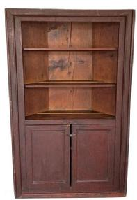 "RM1045 Early 19th century New York State, open top Corner Cupboard in the original dry dark red surface, with two plank doors. three wide board back, plate rails on each shelf, the wood is white pine square head nail construction. Circa 1820 Measurements are: fits a 34 1/2"" corner and"