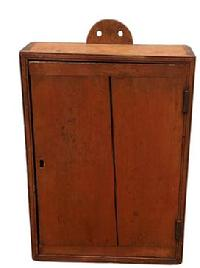 F86 19th century New England single door hanging Cupboard in original red with a tombstone back for hanging. The door is one board with bread board ends, double bead on front Case, with a dovetailed case