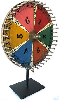 "F25 Early 20th century table top Gaming Wheel with six colorful sections and nickeled posts, mounted to a contemporary iron stand. Measurements: 14"" dia. Provenance: American Primitive Gallery, New York, New York; A Pennsylvania collection."