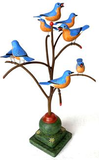 F565 American, 20th Century Folk Art Bird Tree, with eightbeautiful polychrome painted and hand  carved wooden Blue Birds   resting on a steamed and bent branchs in a colorful bas