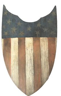"RM1022  Outstanding Patriotic Shield with 13 star American flag In the United States, wooden patriotic shields were first designed to commemorate the Centennial International Exhibition of 1876 (a World's Fair held in Philadelphia, Pa., to celebrate the 100th anniversary of the signing of the Declaration of Independence). This circa 1875 hand-painted patriotic shield (24""W x 15 1/2""H) is made of pine."