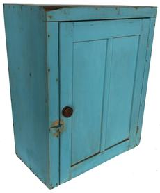 "RM1036 19th century Hanging Cupboard, in original blue paint, found in New England circa 1880.  A great cupboard, with the look of 19th century with double flat panel door which still retains its original iron hinges. The interior has three shelves. It is round nails construction with some square head nails. Measurements are: 26"" tall x 21 1/2"" wide x 12"" deep"