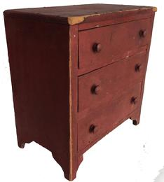 "E330 19th century Eastern Shore Maryland  Minature three drawer Chest, with the original red paint  original wooden knobs nice high cut out cut out shape foot, nail construction with small  square head nails. measurements are. 12"" wide x 12 3/4"" Ttal x 7 3/4"" deep"