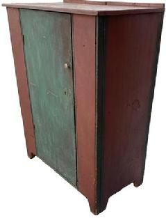 Mid 19th century PA single door storage cupboard. Door is one single board wide with nice cut out at base. It has half inch beaded molding on both sides of door and outer front corners. It has all square head nail construction. In early red and teal paint over the original red. Ca 1840-1850.