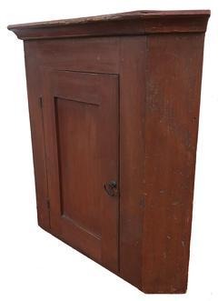 D580 19th century Pennslyvania hanging Cupboard, original red paint, Single panel door, The interior is all natural, with applied cove molding at the top