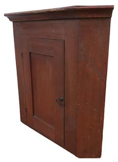 "D580 19th century Pennslyvania hanging Cupboard, original red paint, . The interior is all natural, with applied cove  molding at the top beautiful back boards helding place with squard head nails  Measurements are: 27 1/2"" tall x 21"" corner"