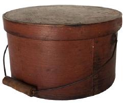 RM337 19th century New England Bail Handle Pantry Box with the original dry red paint ,with over lapping bentwood sides, secured with small metal tacks. The sides of the Box are fitted with a pair of oval stamped tin handle mounts. Fitted with an arched wire swing handle with wooden hand grips.