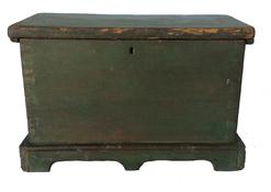 "B374 Mid 19th century Miniature Blanket Chest from Eastern Shore Maryland, (Salisbury MD) in early old green over the original red paint, dovetailed case, with an applied cut out base, with a center drop apron, in front and back, Measurements are 7 1/4"" deep x 13 1/4"" wide x 8 1/2"" tall"