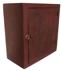 "C133 Early 19th century  Hanging Cupboard  from New England  with the original dry red paint,  the wood is pine, square nail construction, two board door with ""bread-board ends"" to keep door from warping.  circa 1820 -1840"