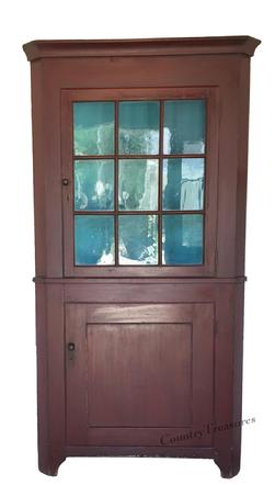 "D335 Pennsylvania Softwood Two Part Corner Cupboard. Cove molded cornice, single nine pane glazed upper door above a single lower paneled door and cut out bracket feet. Old red paint. 83""h. x 43-1/2""w. x 22""d."
