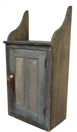 "C75 19th century Pennsylvania Hanging Cupboard , with a double panel door,with scalloped sides on very top of cupboard,  unusual form, nice dry original paint Measurement are: 20 1/4"" wide x 13"" deep x 41 3/4"" tall"