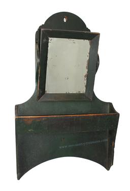 "D87 Early 19th century hanging Saving Wall Box with tilting looking glass, in the most beautiful dry Windsor green paint unclean surface. One board construction with a tombstone arched top, Chippendale scalloped corners, all square nail construction, with a high arched cut away bottom. Under the looking glass is a canted box for holding straight razor and comb. Measurements are:16 1/2"" wide x 3 1/4"" deep x 27 1/4"" tall"