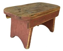 "F465 Early 19th century Lancaster County Pennsylvania, mortised  stool, in old red paint, high arched cut out sides, with splayed legs  and  aprons on both sides,  one board  pine wood,  square head nail construction .Measurements are 15"" long x 8 1/2"" tall x 81/2' wide"
