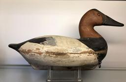 E299 Canvasback decoy carved by John (�Jack�) McKenney (1889-1973) from Chestertown, MD.  Brand on the bottom reads:  �E. A. VOSHELL� who was Mr. McKenney�s father-in-law.  Bill Shauber, another carver from Chetertown, MD, states Mr. McKenney was his Uncle and that he only carved approximately 500 birds in his lifetime, mostly during the 1950s.  This decoy retains both its wooden keel (with lead lining the bottom outer portion of the keel) and its original coat of paint with the wear around the middle section of the bird being attributed to significant use in icy conditions.