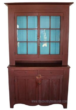 JR2 Pennsylvania two piece Stepback Cupboard, with original dry red painted surface, 12 wavy glass window lights. The interior of cupboard has a warm blue painted interior .