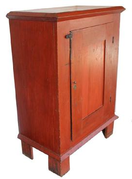 B412 Mid 19th century single door Milk Cupboard, with original bittersweet  red paint . Applied molding on top held in place with wooden pegs , one board construction , with a single panel door, nice high  base, three board ba ck, circa 1840 � 1850