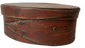 F38 mid-19th century. Bentwood construction having tacked lap joints. Oval pantry box in the original dry red paint with finger laps.