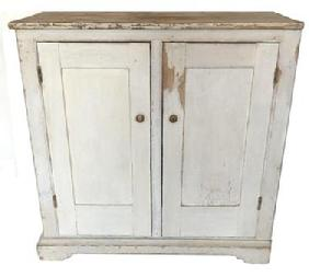 D560 Early 19th century two door storage Cupboard, circa 1810 - 1820 in old white paint. Two panel doors full mortised and pinned one board construction. The wood is all white pine with an applied base and pit-sawed back boards held in place with square head nails. This cupboard was made to fit in corner.