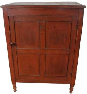 D179 Early 19th century Lancaster County Pennslyvania four panel door Cupboard,in the original red paint, resting on four Sheraton turned feet. single panel on each side, with two chenfered panels in the back . Original turn knob and hardware, the wood is poplar and cheery circa 1820-18230