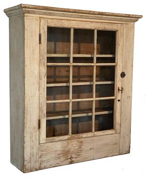 200 Early 19th Century hanging flat wall cupboard from Western Pennsylvania in original white paint, having a single door with 9 window-lites and a small chamfered molding around the top.  The door is full mortised and pegged with early wavy, bubbled glass.  There are three reverse graduated shelves inside (Top to bottom: 7� deep, 6 ¾� deep & 5 ½� deep) which allows better access to the inside bottom of the cupboard.  All square nail construction. Measurements: 39� tall x 33 ¼� wide case (35�wide at molding) x 9 ½� deep (10 ¾� deep at molding)