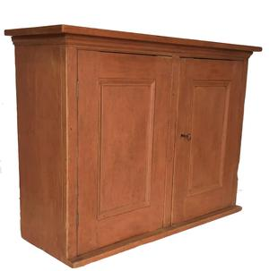 A487 Mid 19th century two door hanging  Pennsylvania Cupboard , with original salmon paint,  with two panel doors, full mortised and pinned, with a small applied cove molding on the top  circa 1850