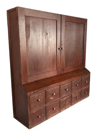 "D531 Late 18th century, New England Hanging Apothecary/ Desk in origininal red painted surface.  with two doors over ten drawers,  with fold out writing surface. Dovetailed case, white pine one board construction, tee and square head nail construction, applied picture frame molding on ends, with  double beaded drawer dividers Measurements are:  45 1/4"" tall x 44 1/2"" wide x 11 1/2"" deep"