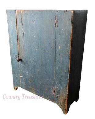 "C411 18th century Pennslyvania Cupboard , with the original indigo blue paint , plank door construction, with dovetailed case, single plank door with interior beaded baton and iron H-hinges, beded stiles and arched cut out feet 47"" high x 36 1/2 "" wide x 14"" deep"