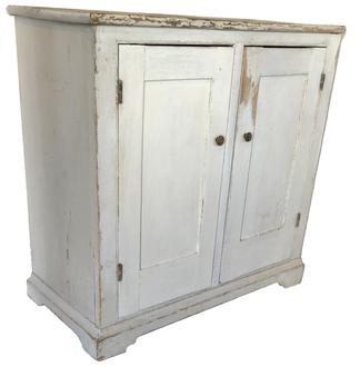 "D560 Early 19th century two door storage Cupboard, circa 1810 - 1820  in old white paint. Two panel doors full mortised and pinned one board construction. The wood is all white pine with an applied base and pit-sawed back boards held in place with  square head nails. This cupboard was made to fit in corner. Measurements are: 17 1/4"" deep x 36"" wide x 36"" tall"