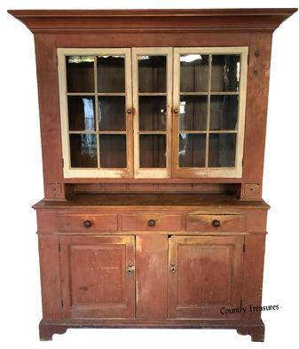 "Epic 19th century Pennsylvania Perry Co. two part painted pine Dutch Cupboard. The upper section with a wide cornice above two glazed doors, with original old wavy glass, with a rare center glazed divider, with two small candle drawers ( one being divided for spices) at bottom, with a 5� tall pie shelf.  The base has an dovetailed case with three dovetailed drawers above two raised paneled doors resting on an tall dovetailed applied bracket base. Retaining it's original salmon painted case with oyster white painted doors and glazed panel divider. This cupboard is made of white pine (all one board construction) with large over-sized pegs with �Tee� and  �Square� head nails circa 1790-1820 89 1/2"" high x 72"" wide  18 1/2"" deep"