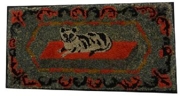 Y217 An outstanding example of American folk art, This  hooked rug patterns of the later 19th century, and it was probably hooked sometime around 1890. This rug features a princely Tabby cat on a red rug, A floral garland surrounds the cat, Strips of wool cloth were used for the hooking and it was done on burlap.The rug measures 19 1/2� x 37 3/4�