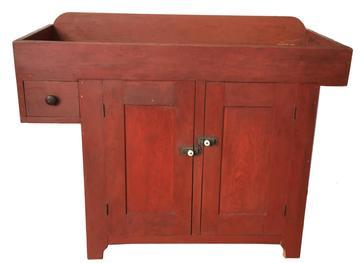 D234 19th century Pennslyvania York County , over hanging drawer Drysink, in the original red paint, open well, over two panel door which are mortised and pegged, nice high cut out foot, with solid ends, with a single dovetailed drawer