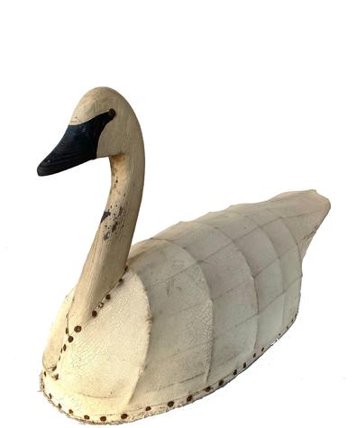 An early American confidence decoy of a swan featuring a carved and painted wooden head and neck attached to a body of canvas over a wood and metal frame Branded on bottom Cedar Is. Gun Club A great example of American primitive folk art - graceful lines and handsome design! Measurements 31� long 11� wide 16 ½� tall