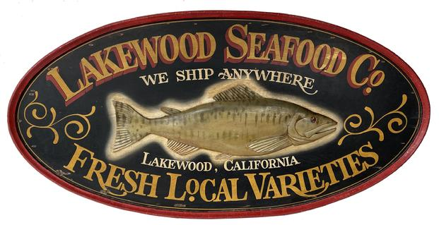 "F151 Early 20th century beautiful wooden Double Sided Seafood Co. Hanging Wood Advertising Sign. Large oval double sided sign centered with a relief carved fish and reads ""Lakewood Seafood Co., We Ship Anywhere, Fresh Local Varieties, Lakewood, California"". Very nice overall condition, minor paint flaking, missing some of the raised molding on the left edge of one side Measurements are: 30"" high x 60"" wide x 2 1/4"" deep"