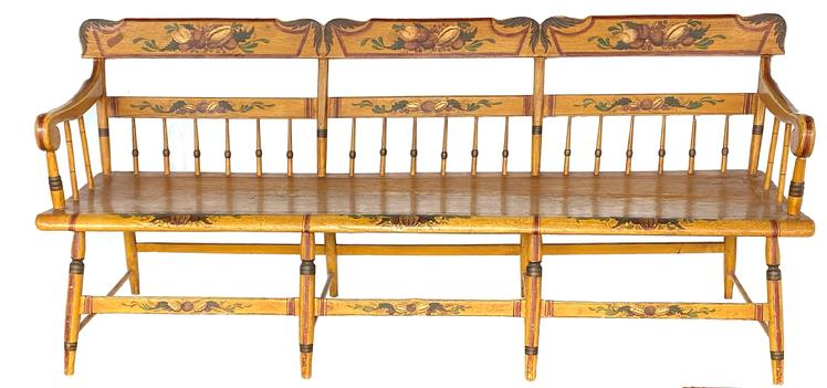 Paintted, Pennsylvania, plank-seat settee of the mid-19th century (1845-65), in the half-spindle-back style with an angel wing crest rail. The mustard yellow with yellow, brown and black striping. The theorem-like registers on the crest rails are typical of rural Pennsylvania chairs and benches. There is a large bell flower in the center, flanked by a tulip and various flora. On each side register there are grapes, flanked by another bell flower and more foliage. The overall result is a pleasing example of Pennsylvania German Folk Art on a piece of rural-made, paint- decorated furniture.  Condition: Minimal, expected wear. Excellent, original surface.